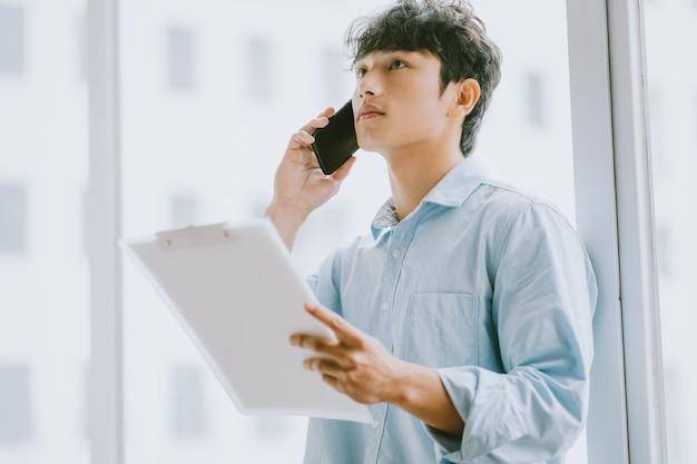 Asiatischer geschäftsmann ruft an, um über die arbeit am fenster zu diskutieren