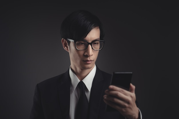 Asiatischer geschäftsmann scannt gesicht durch smartphone unter verwendung des gesichtserkennungssystems.