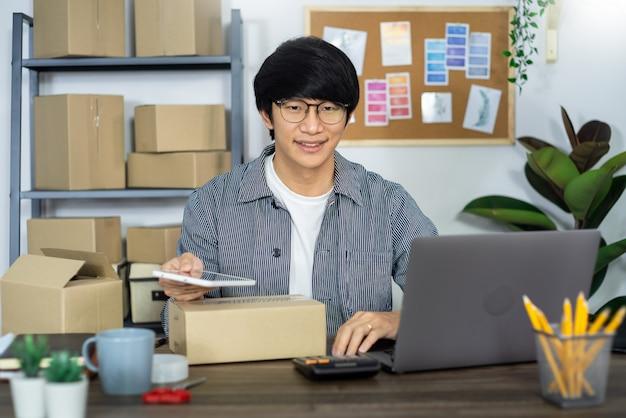 Asiatischer geschäftsmann startup kmu unternehmer oder freiberuflich in einem karton arbeiten bereitet vorbereitung box für kunden, online-verkauf, e-commerce, verpackung und versandkonzept.