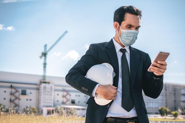 Asiatischer geschäftsmann trägt gesichtsmaske anruftelefon im freien vor ort bau