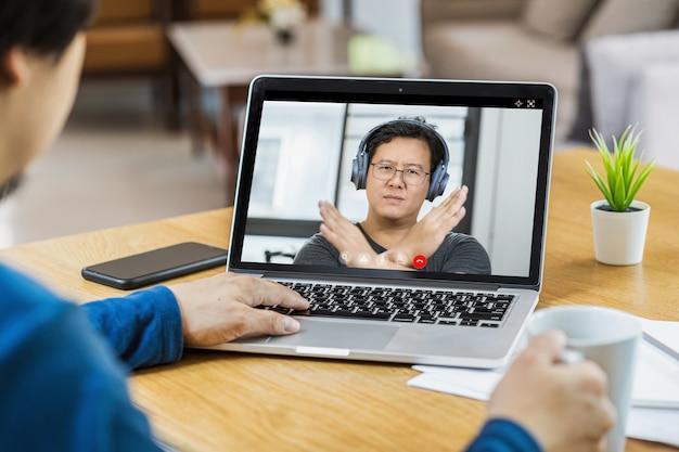 Asiatischer geschäftsmann trifft sich und stimmt nein mit teamwork-kollege in videoanrufkonferenz ab