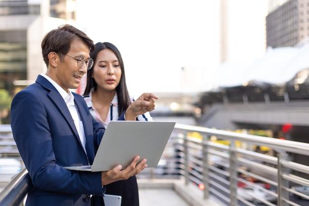 Asiatischer geschäftsmann und frau, die an laptop-computer arbeiten, die außerhalb des bürogebäudes stehen.