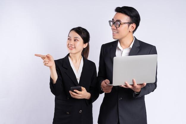 Asiatischer geschäftsmann und geschäftsfrau mit laptop auf weißem hintergrund