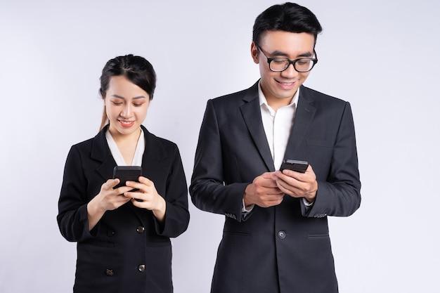 Asiatischer geschäftsmann und geschäftsfrau mit smartphone auf weißem hintergrund