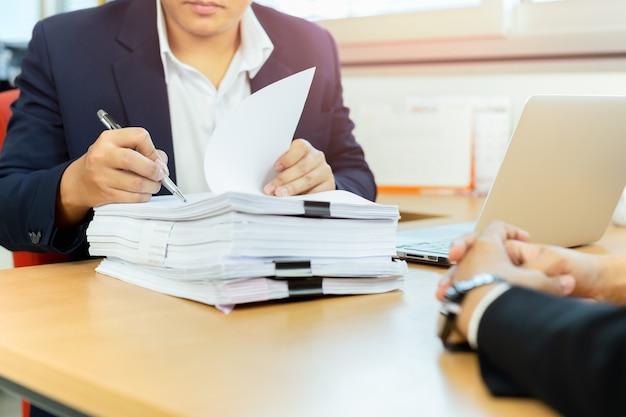 Asiatischer geschäftsmann und seine unterzeichnende dokumentenarbeit des stellvertretenden sekretärs im büro.