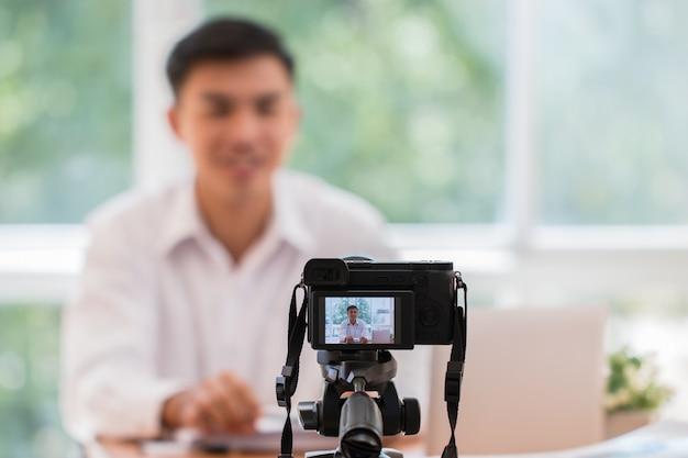 Asiatischer geschäftsmann vlogger, der onlinekurs notiert