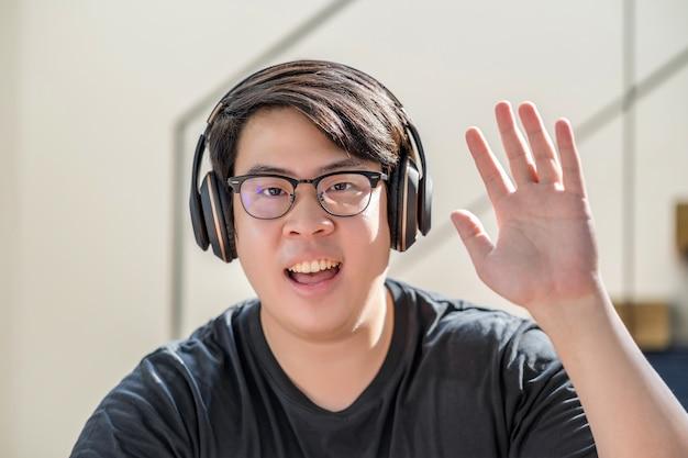Asiatischer geschäftsmann winkt mit der hand, um hallo zu sagen, wenn er einen videoanruf an einen freund mit sozialer distanz macht