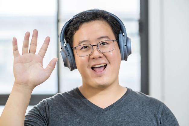 Asiatischer geschäftsmann winkt mit der hand, um hallo zu sagen, wenn er einen videoanruf mit einem freund mit sozialer distanzierung macht