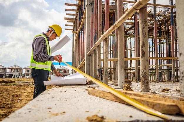 Asiatischer geschäftsmannbauingenieurarbeiter im schutzhelm und im blaupausenpapier zur hand, die betonboden auf hausbaustelle messen
