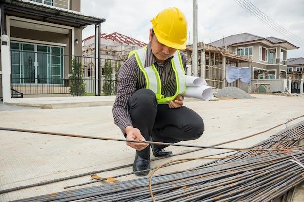Asiatischer geschäftsmannbauingenieurarbeiter im schutzhelm und im blaupausenpapier zur hand, die stahlstange auf hausbaustelle betrachtet