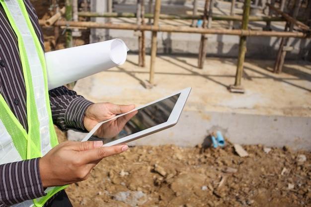 Asiatischer geschäftsmannbauleiter und ingenieurarbeiter im schutzhelm halten blaupausenpapier zur hand unter verwendung des tablet-computers auf der baustelle