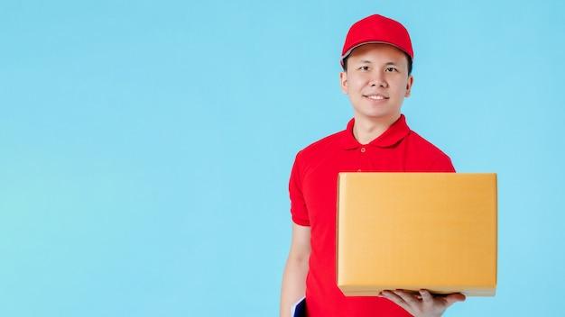 Asiatischer glücklicher lieferer, der ein rotes hemd trägt, das beim halten von papierpaketkästen lokalisiert auf blauem farbhintergrund mit kopienraum ein rotes hemd trägt. konzept des postzustelldienstes.