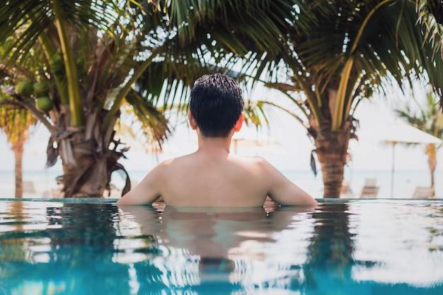 Asiatischer glücklicher mann, der im swimmingpool im resorthotel am meereshintergrund schwimmt und entspannt.