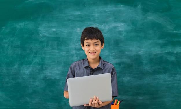 Asiatischer glücklicher schuljunge, der laptop auf schwarzem brett hält