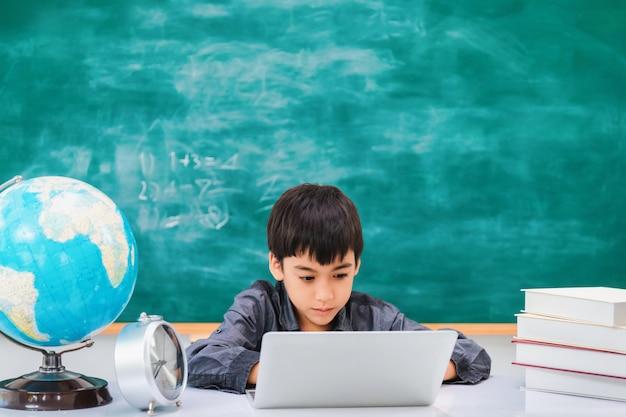 Asiatischer glücklicher schuljunge, der laptop auf tafel verwendet