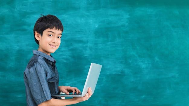 Asiatischer glücklicher schuljunge, der laptop hält
