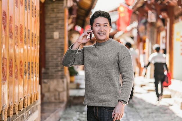 Asiatischer glückmann des porträts, der intelligenten handy für das nennen verwendet