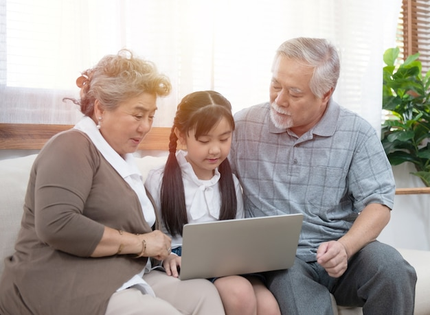 Asiatischer großelternteil mit jungem enkelkind, das auf sofa sitzt und zusammen spielt
