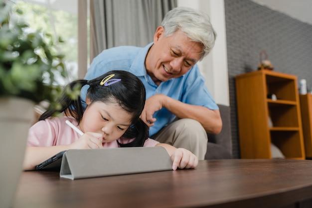Asiatischer großvater unterrichten die enkelin, die zu hause hausaufgaben zeichnet und tut. der ältere glückliche chinese, großvater entspannen sich mit dem jungen mädchen, das zu hause auf sofa im konzept des wohnzimmers liegt.