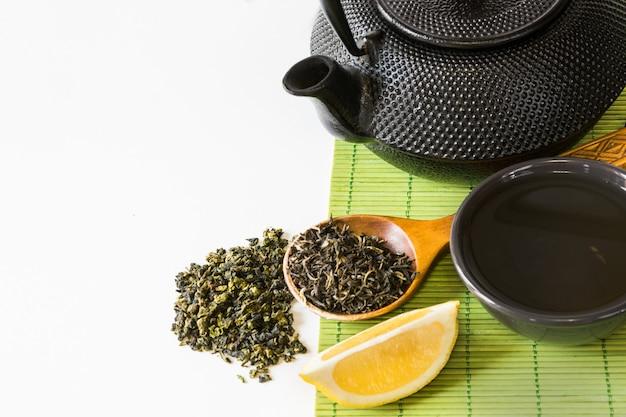 Asiatischer grüner teesatz auf bambusmatte mit getrocknetem grünem tee im löffel.
