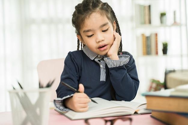 Asiatischer grundschulestudent, der hausarbeit im haus studiert