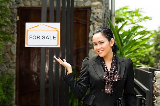 Asiatischer grundstücksmakler, der ein neues haus darstellt
