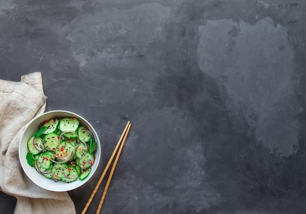 Asiatischer gurkensalat mit roten zwiebeln, chilipfeffer und schwarzem sesam in weißer schüssel auf grauem betonhintergrund. draufsicht mit platz für text.