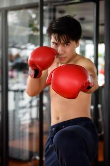 Asiatischer gutaussehender mann, 20 bis 30 jahre alt, übend muay thai am eignungsportgymnastik.