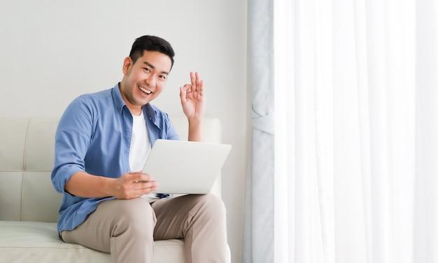 Asiatischer gutaussehender mann, der mit laptop-computer im wohnzimmer glücklich und im lächelngesicht arbeitet