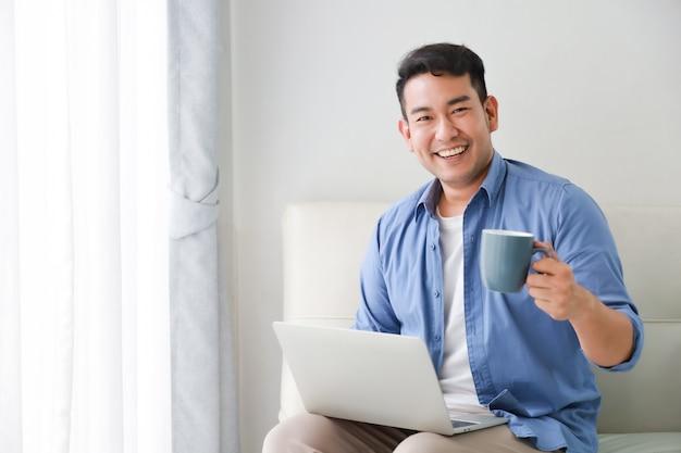 Asiatischer gutaussehender mann, der mit laptop-computer und getränkkaffee im wohnzimmer glücklich und im lächelngesicht arbeitet