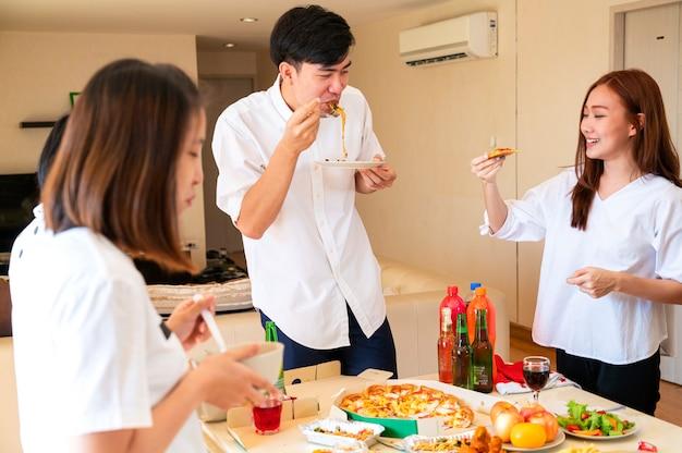 Asiatischer gutaussehender mann, der pizza isst, während in neujahrsessenparty im modernen wohnzimmer mit bestem freund bleibt. neujahrsparty, freund, dinnerparty-konzept