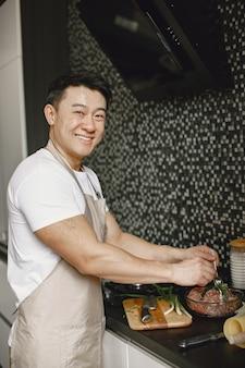 Asiatischer gutaussehender mann, der zu hause kocht. mann, der fleisch in der küche vorbereitet.
