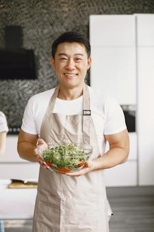 Asiatischer gutaussehender mann, der zu hause kocht.