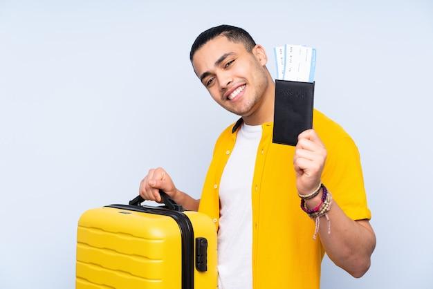 Asiatischer gutaussehender mann lokalisiert auf blau im urlaub mit koffer und pass
