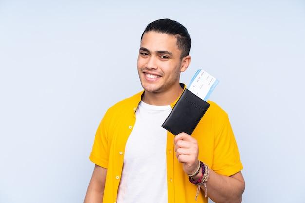 Asiatischer gutaussehender mann lokalisiert auf blauer wand glücklich im urlaub mit pass und flugtickets
