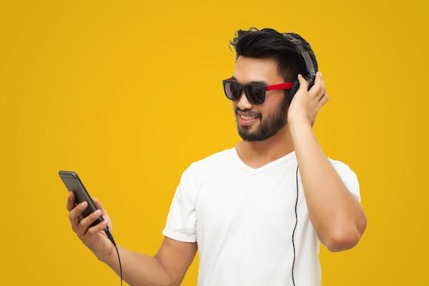 Asiatischer gutaussehender mann mit einem schnurrbart, lächelt und lacht und verwendet intelligentes telefon