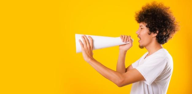 Asiatischer gutaussehender mann mit lockigem haar, das er unter verwendung des weißen lautsprecherpapiers ankündigt