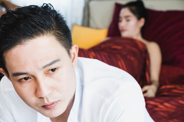 Asiatischer gutaussehender mann trostlos, sorgte sich, nachdem sex mit schöner frau im bett gehabt hatte