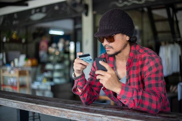 Asiatischer hipster-mann hält kreditkarten und benutzt handys für online-einkäufe.