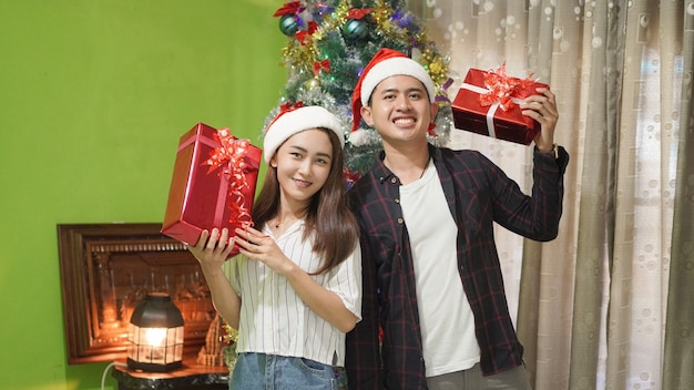 Asiatischer hübscher bruder und schöne schwester bringen glückliche geschenke zu weihnachten