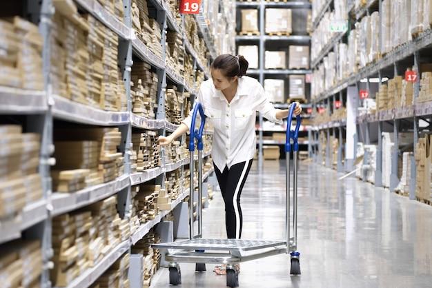 Asiatischer hübscher kunde, der produkte im speicherlager sucht.