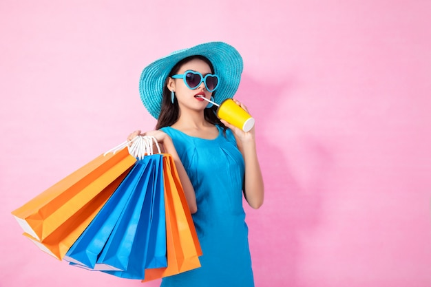 Asiatischer hübscher mädchen sommer, der einkaufstaschen hält, während das wasser und sonnenbrille trinken, die weg auf hintergrund lokalisiert schauen.