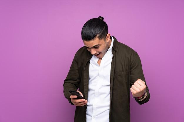 Asiatischer hübscher mann auf blauer wand überrascht und eine nachricht sendend