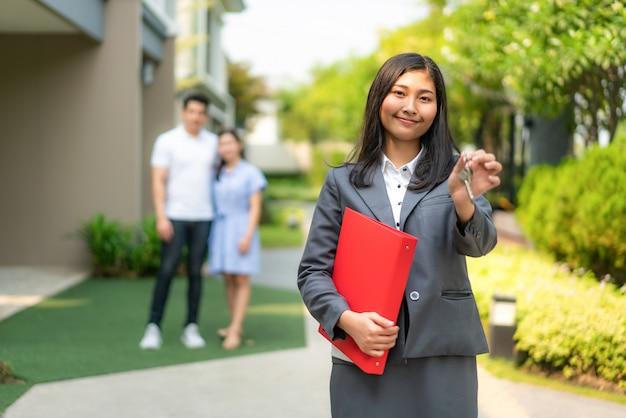 Asiatischer immobilienmakler oder maklerin, die lächelt und rote datei mit hausschlüssel zeigt