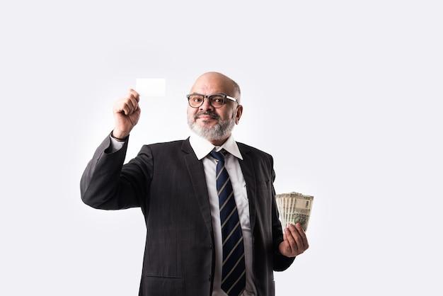 Asiatischer indischer alter geschäftsmann, der geldscheine, geldfächer, leere elektronische debitkarte hält