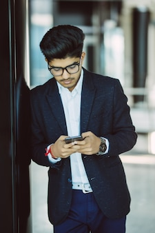 Asiatischer indischer geschäftsmann, der unter verwendung des smartphones beim stehen im büro eine sms sendet
