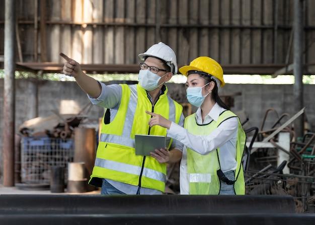 Asiatischer ingenieur, der den produktionsprozess auf der fabrikstation überprüft, indem er während der covid-19-pandemie eine sicherheitsmaske trägt, um die fabrik vor verschmutzung und viren zu schützen