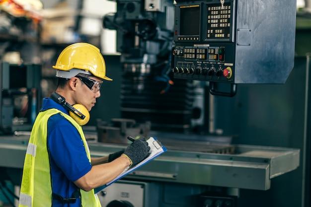 Asiatischer ingenieur, der die maschine in der fabrik prüft, arbeiter, der notiz mit listenpapier schreibt.