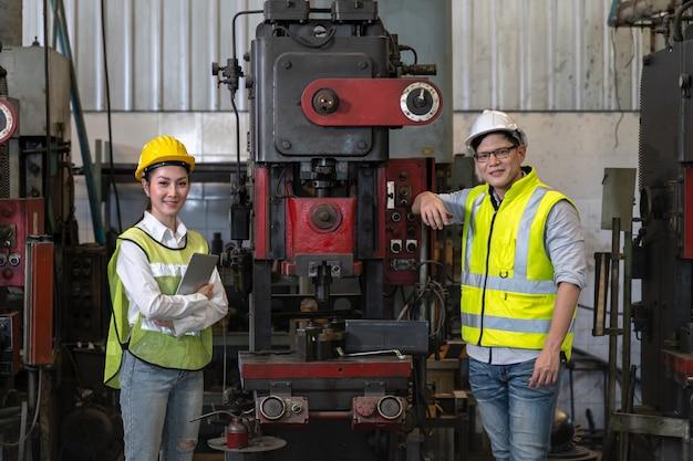Asiatischer ingenieur, der produktionsprozess auf fabrikstation prüft. industriekonzept