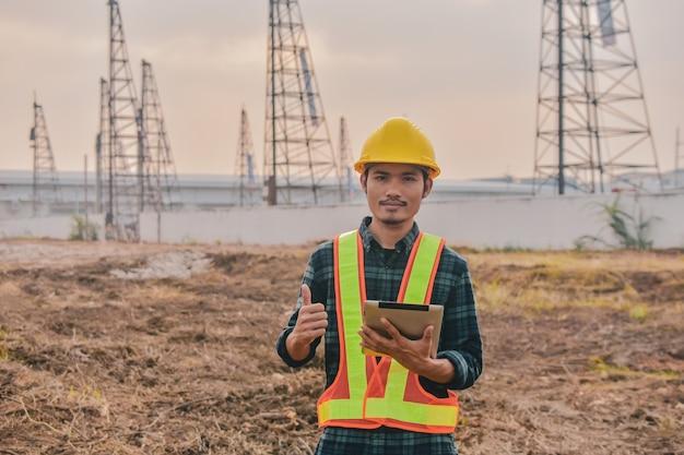 Asiatischer ingenieur, der tablett verwendet, das auf baustellenkonstruktion arbeitet